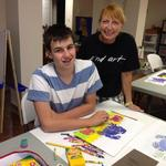 Carol guides 8th grader Joe in art-making.  Joe was a featured artist at a Student Art Show.